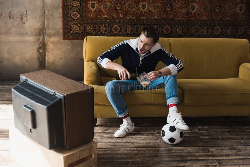 rozkrzyczany młody człowiek w roczniku odziewa z balową dopatrywanie piłką nożną na starym tv i dolewania piwie obrazy royalty free