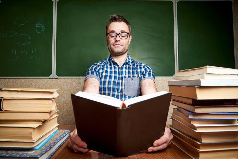 Rozkudłany młody człowiek czyta książkę przy stołem z stosami książki na tle blackboard w szkłach obrazy stock