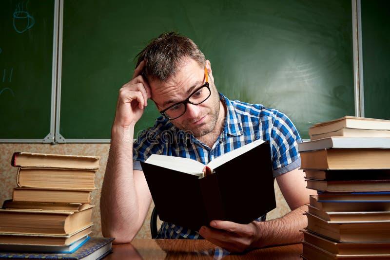 Rozkudłany nieogolony młody człowiek czyta książkę przy stołem z stosami książki w szkłach zdjęcie stock