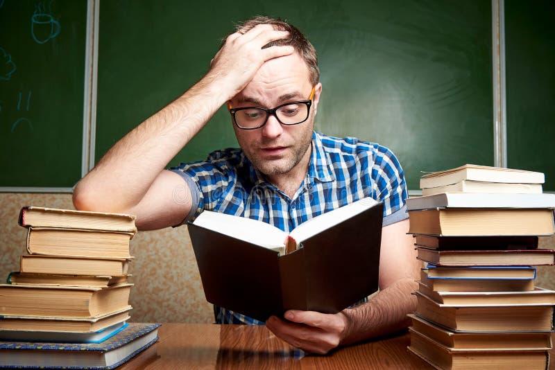 Rozkudłany nieogolony młody człowiek czyta książkę przy stołem z stosami książki w szkłach fotografia royalty free