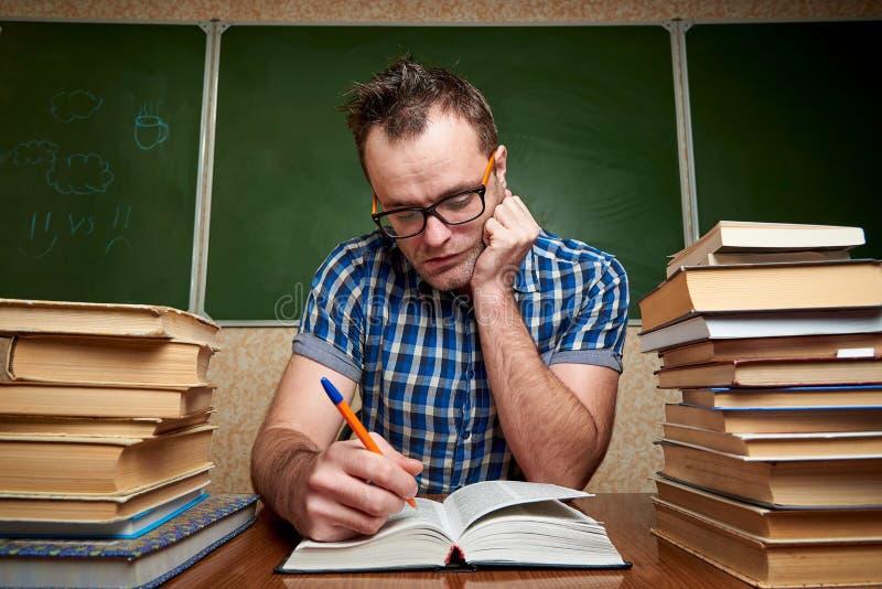 Rozkudłany nieogolony młody człowiek czyta książkę przy stołem z stosami książki w szkłach zdjęcia stock