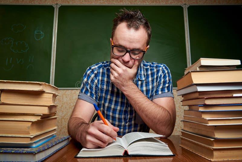 Rozkudłany nieogolony młody człowiek czyta książkę przy stołem z stosami książki w szkłach fotografia stock