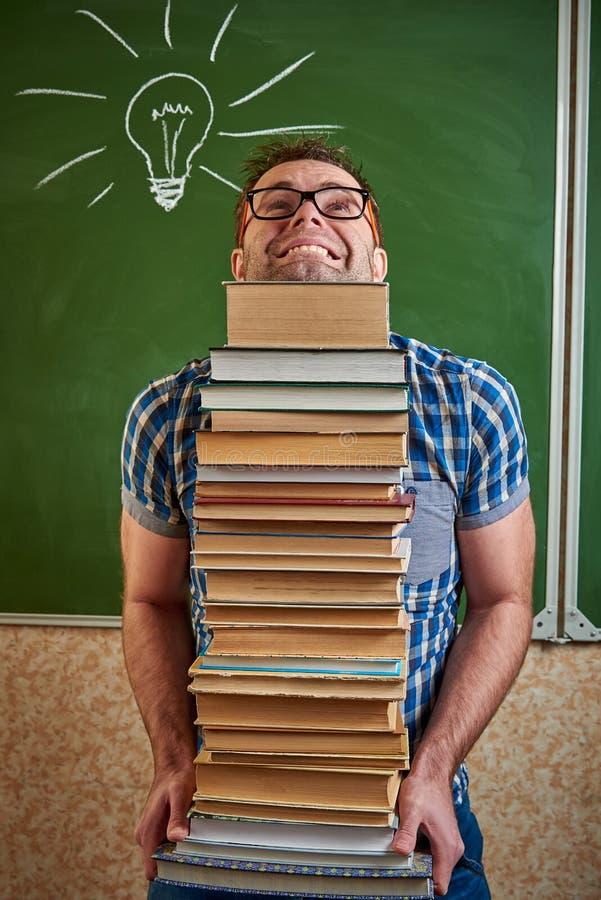 Rozkudłany nieogolony młody człowiek w szkłach trzyma ciężką stertę książki zdjęcie royalty free