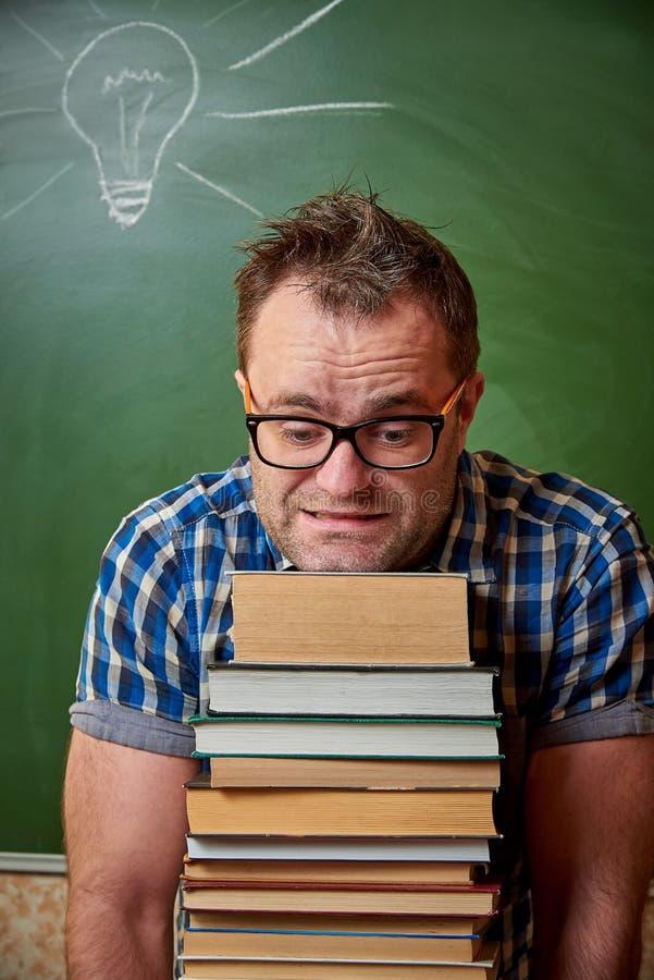 Rozkudłany nieogolony młody człowiek w szkłach trzyma ciężką stertę książki fotografia stock