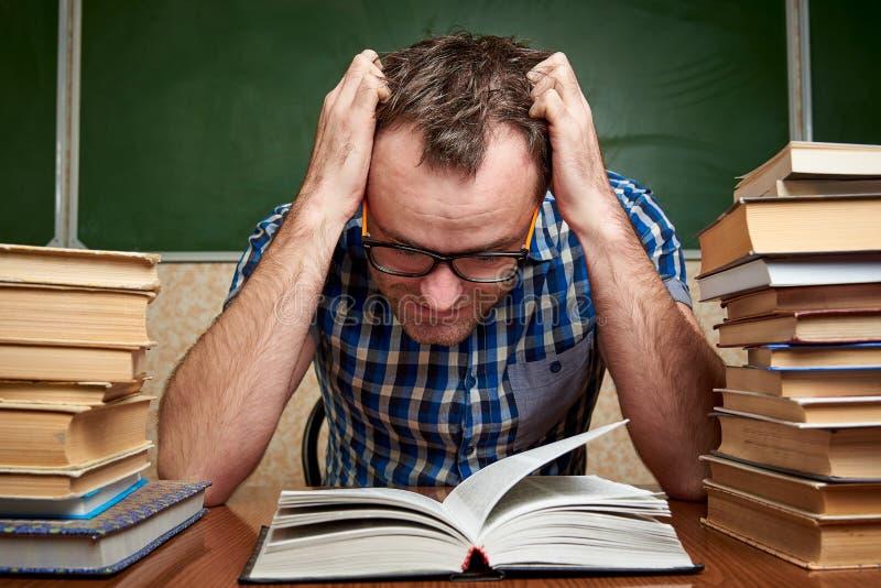 Rozkudłany zmęczony nieogolony młody człowiek z szkłami trzyma jego głowę i czyta książkę przy stołem z stosami książki fotografia stock
