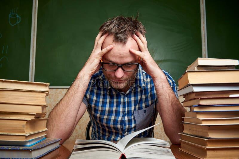 Rozkudłany zmęczony nieogolony młody człowiek z szkłami trzyma jego głowę i czyta książkę przy stołem z stosami książki obrazy stock