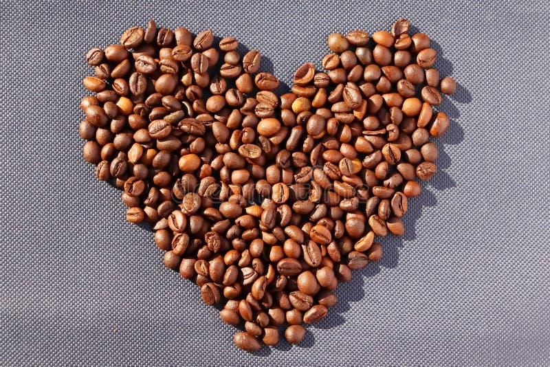 rozlana kawa Adra aromatyczna piec kawa rozpraszająca w postaci serca na kartonie ukazują się w promieniach zdjęcie stock