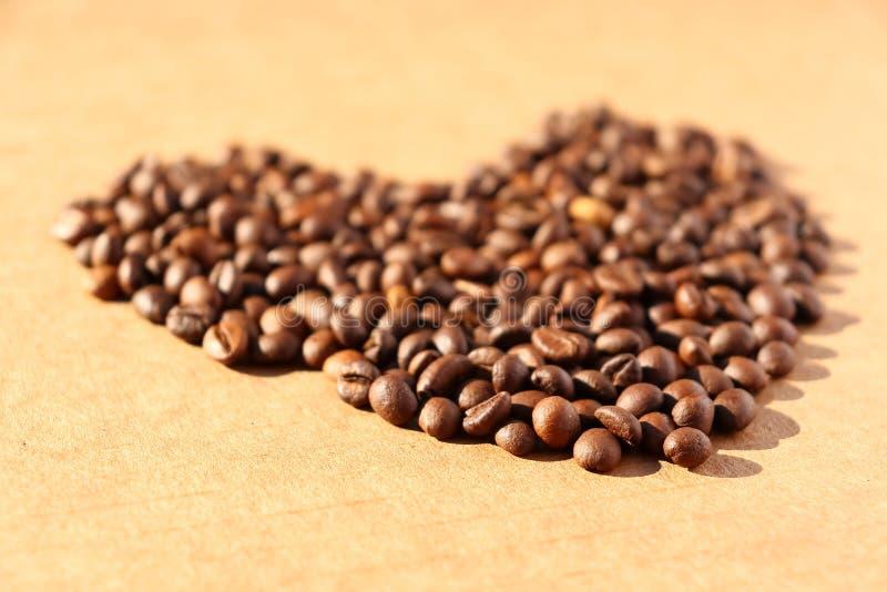 rozlana kawa Adra aromatyczna piec kawa rozpraszająca w postaci serca na kartonie ukazują się w promieniach obrazy stock
