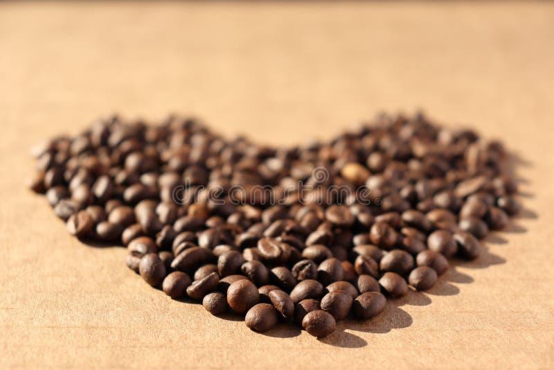 rozlana kawa Adra aromatyczna piec kawa rozpraszająca w postaci serca na kartonie ukazują się w promieniach zdjęcie royalty free