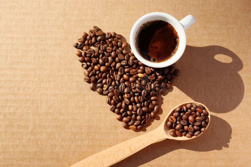rozlana kawa Adra aromatyczna piec kawa rozpraszająca w postaci serca na kartonie ukazują się w promieniach obrazy royalty free