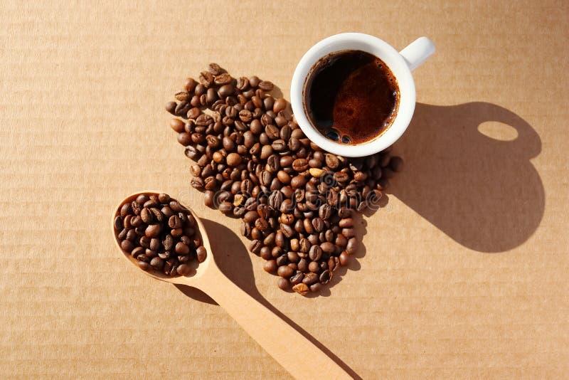 rozlana kawa Adra aromatyczna piec kawa rozpraszająca w postaci serca na kartonie ukazują się w promieniach obraz royalty free