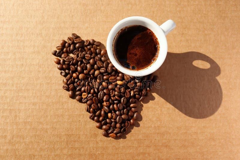 rozlana kawa Adra aromatyczna piec kawa rozpraszająca w postaci serca na kartonie ukazują się w promieniach fotografia royalty free