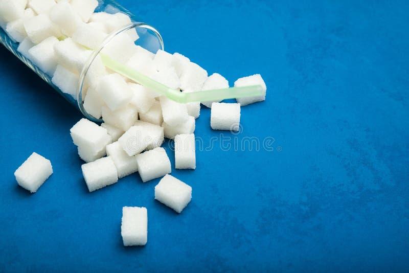 Rozlewający sześciany cukier na błękitnym tle szkło obraz royalty free