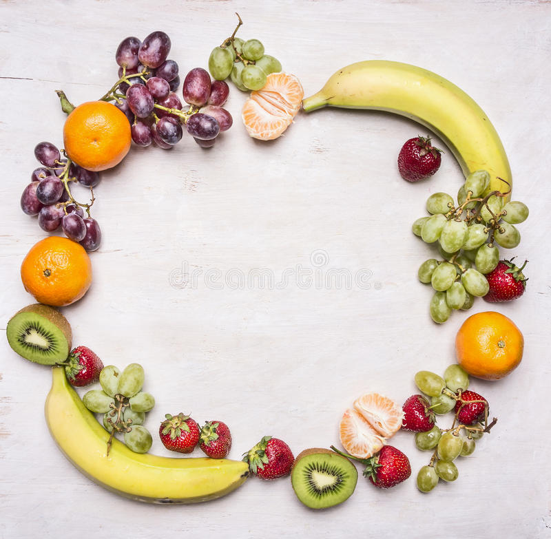 Rozmaitość świeża owoc, bogactwo w witaminach i diety jedzenia rama kłaść out na białym nieociosanym drewnianym tle z przestrzeni zdjęcie stock