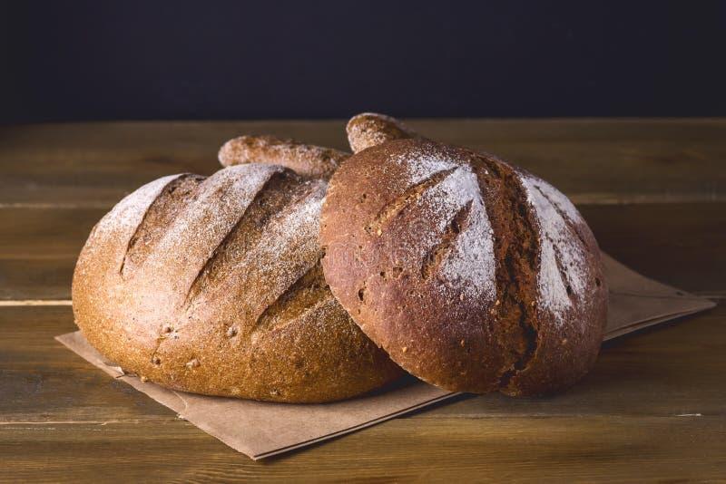 Rozmaitość Próżnuje Świeżego Piec żyta i Całego Zbożowego chleba na Drewnianego tekstury tła fotografii Ciemnej rozmaitości Tonuj zdjęcia royalty free