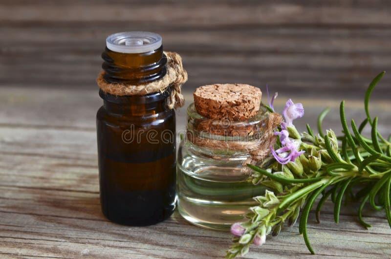 Rozmarynu istotny olej w wkraplacza szklanych butelkach z świeżym zielonym rozmarynowym ziele na starym drewnianym stole dla zdro obrazy royalty free