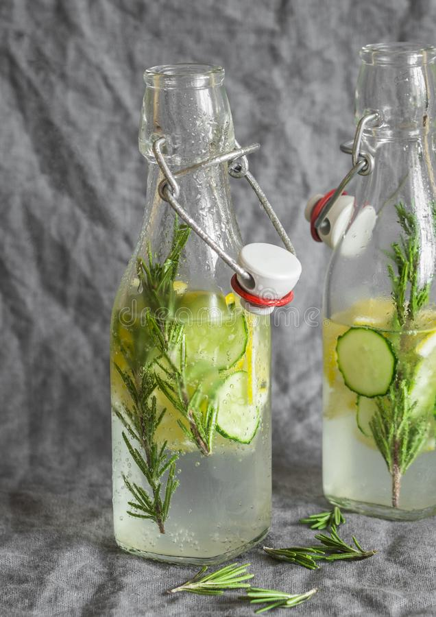 Rozmaryny, cytryna, ogórkowa domowej roboty lemoniada w rocznik szklanych butelkach na popielatym tle fotografia royalty free