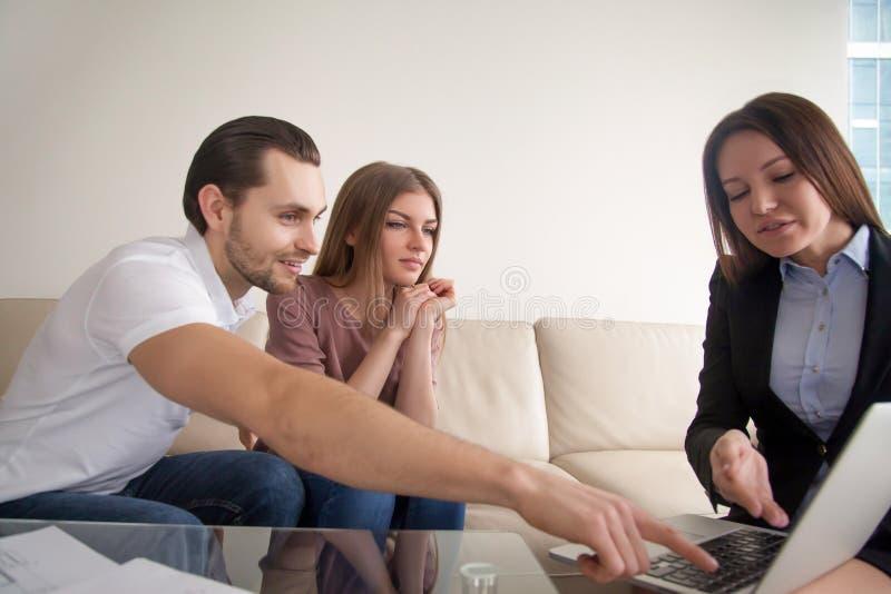 Rozmowa między młodą uśmiechniętą parą i kobieta kierownikiem starzeje się zdjęcia stock