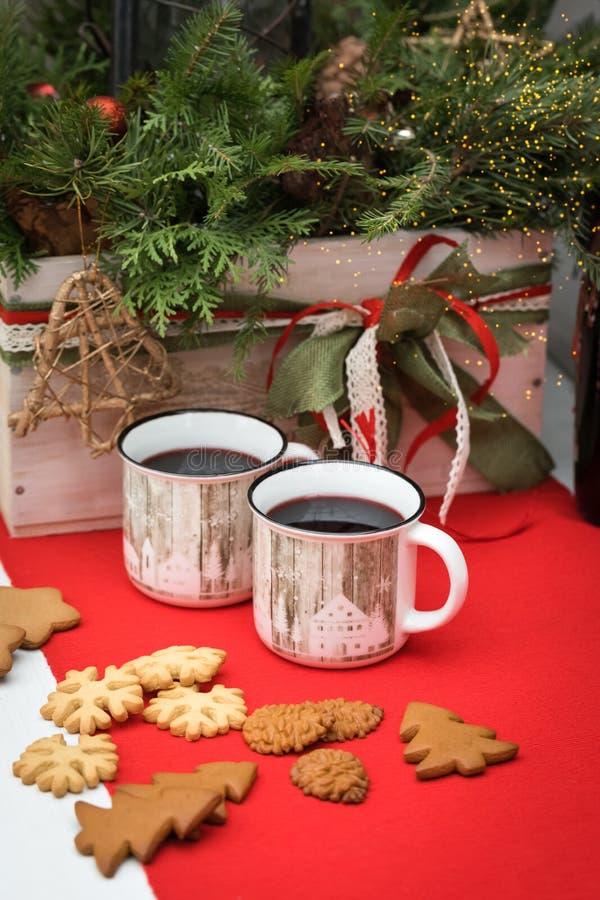Rozmyślający wino w białych ceramicznych kubkach z bożych narodzeń ciastkami na czerwonym obrusie na jedliny dekoracji tle z a, zdjęcia royalty free