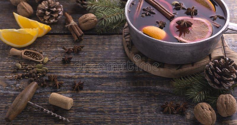 Rozmyślający wino z pikantność i cytrus owoc w niecce na nieociosanym drewnianym stole miejsce tekst zdjęcie royalty free
