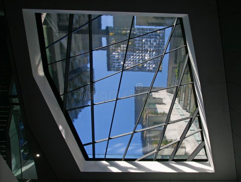 Rozmyci i faliści kontury miasta linia horyzontu nowożytny wieżowiec górują przez szklanego sufitu pod basenem pluskotać wodę na  zdjęcie stock