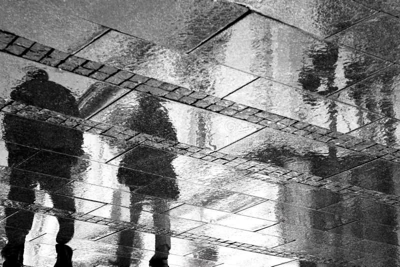 Rozmyci odbicia dwa osoba na dżdżystym chodniczku zdjęcie royalty free