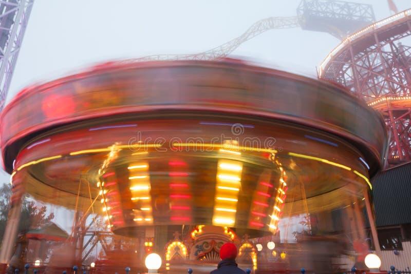 Rozmyty kolorowy carousel w ruchu przy parkiem rozrywkim, wieczór iluminacja Skutek bokeh i długi ujawnienie obrazy royalty free