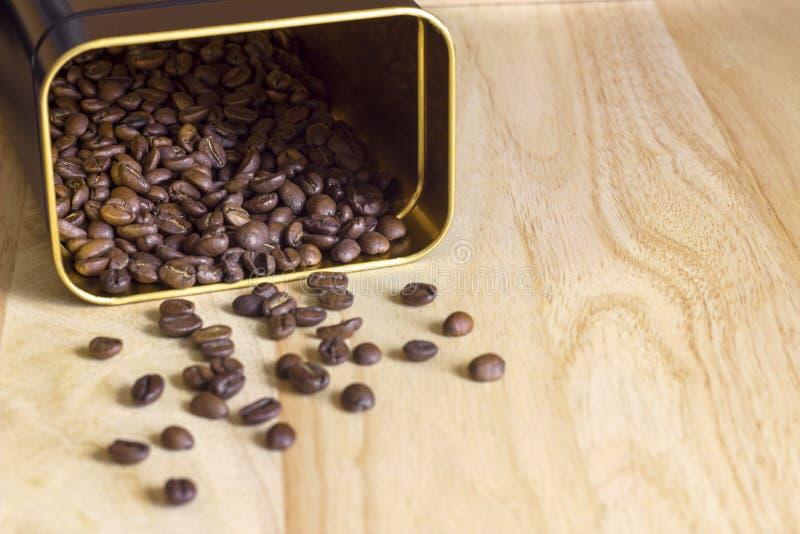 Rozmyty rozrzucony brąz piec kawowe fasole od puszki na lekkiej powierzchni stół fotografia royalty free