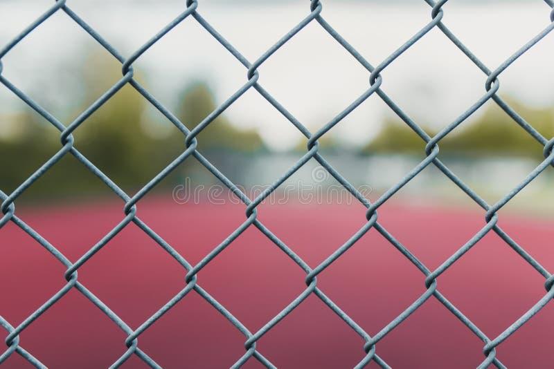 Rozmyty tenisowy sąd z ostrością na ogrodzeniu obrazy stock