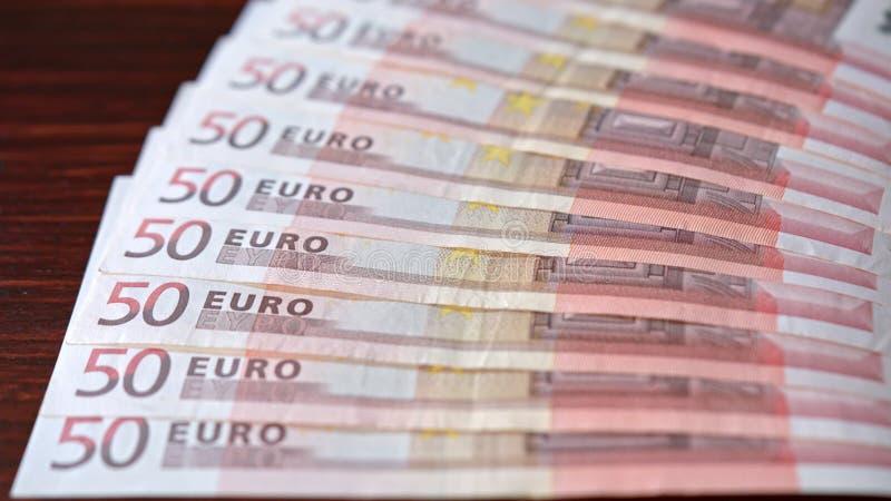 Rozniecony stos Pięćdziesiąt Euro banknotów na stole obrazy royalty free
