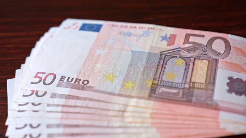 Rozniecony stos Pięćdziesiąt Euro banknotów na stole zdjęcie royalty free