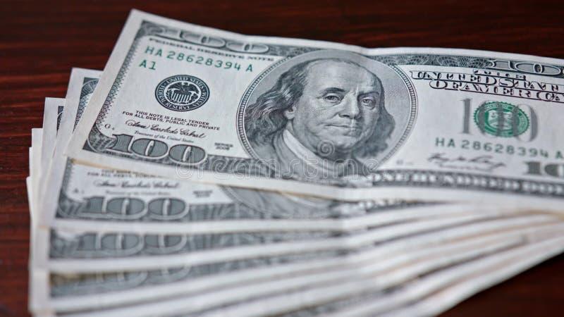Rozniecony stos Sto Dolarowych banknotów na stole fotografia royalty free