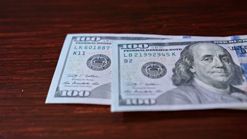 Rozniecony stos Sto Dolarowych banknotów na stole zdjęcie stock