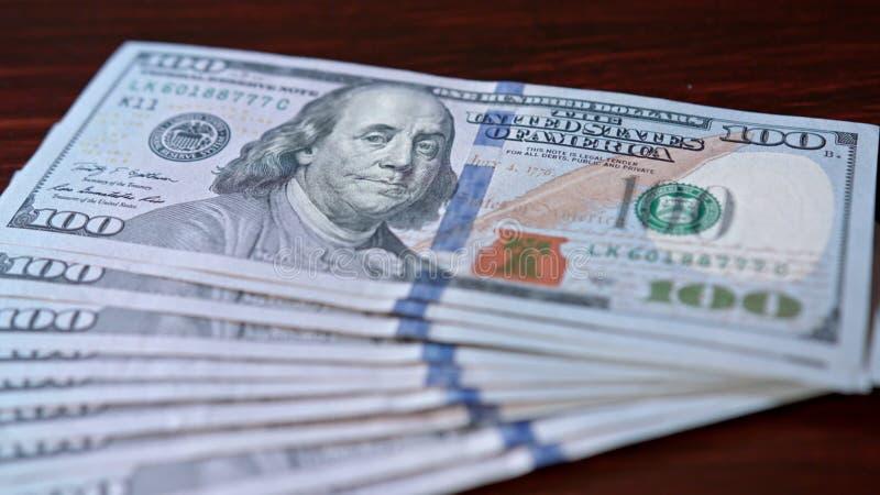 Rozniecony stos Sto Dolarowych banknotów na stole fotografia stock