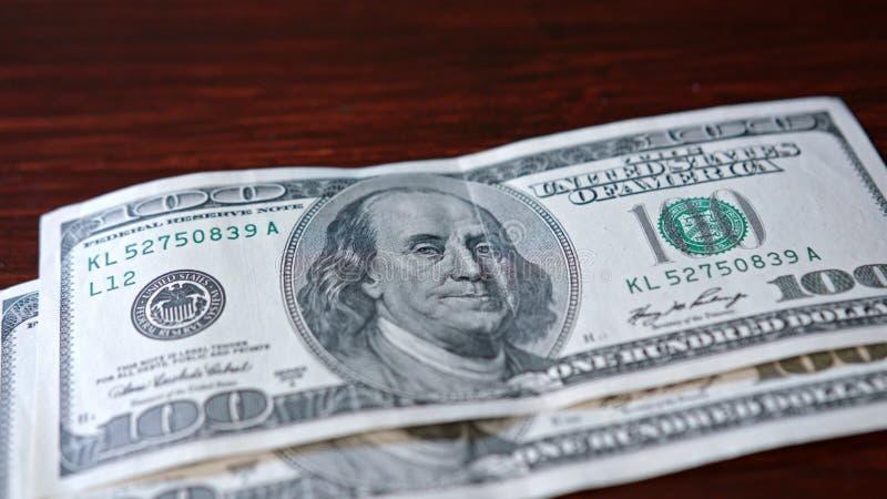 Rozniecony stos Sto Dolarowych banknotów na stole zdjęcia royalty free