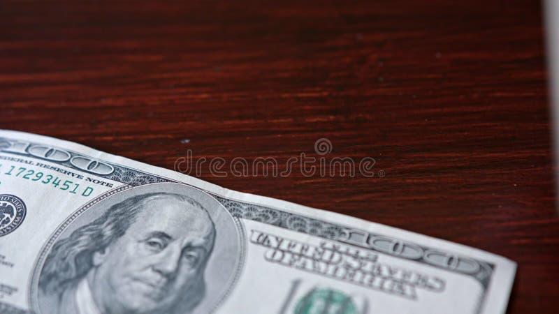 Rozniecony stos Sto Dolarowych banknotów na stole zdjęcie royalty free