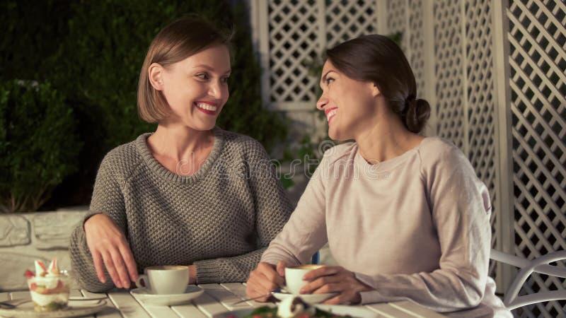 Rozochoceni żeńscy przyjaciele siedzi kawiarni wpólnie, mieć przyjemnego czas, powiązania zdjęcie royalty free