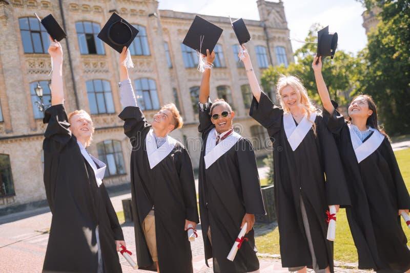 Rozochoceni absolwenci podnosi ich mistrz nakrętki w powietrzu zdjęcia stock