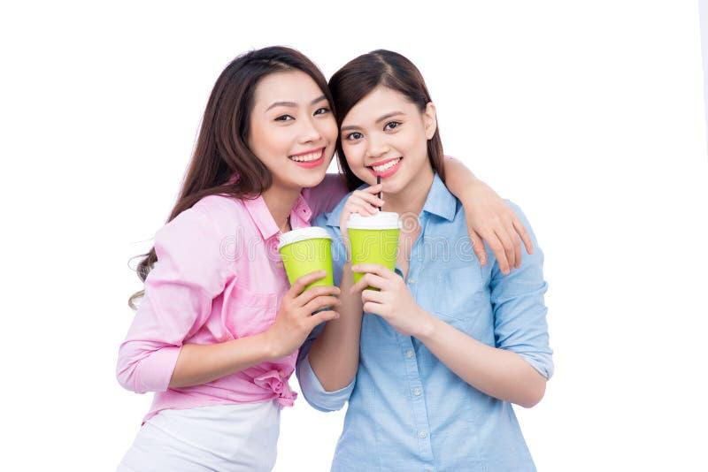 Rozochoceni azjatykci żeńscy przyjaciele trzyma kawowych kubki cieszy się rozmowę zdjęcie royalty free