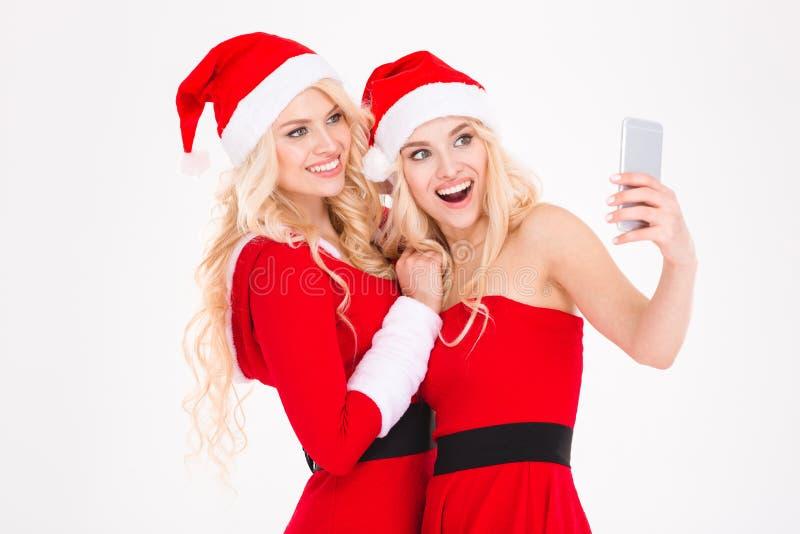 Rozochoceni blondynek siostr bliźniacy robi selfie używać telefon komórkowego fotografia royalty free