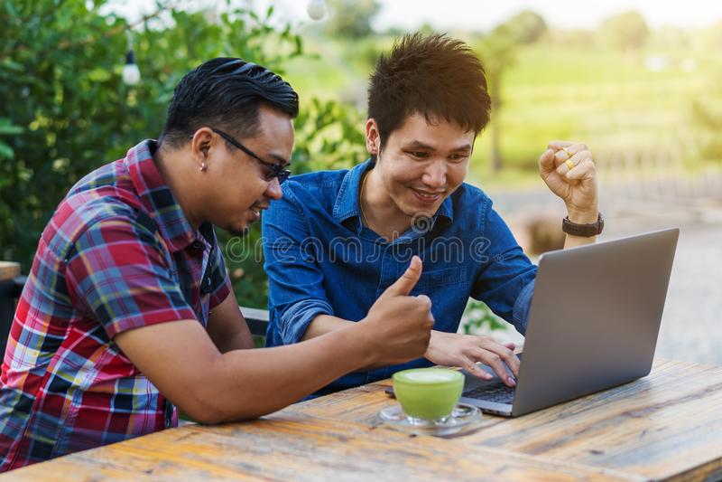 Rozochoceni dwa obsługują używać i pracujący na laptopie obrazy royalty free