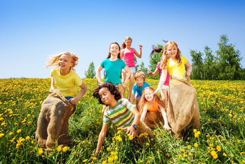 Rozochoceni dzieci skacze w worek sztuce wpólnie zdjęcie royalty free