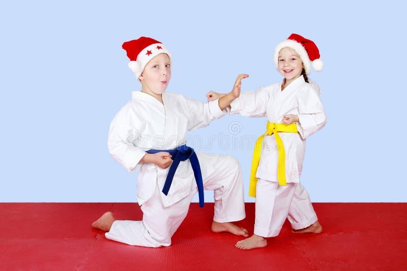 Rozochoceni dzieciaki w nakrętkach Święty Mikołaj robi technika karate zdjęcie royalty free