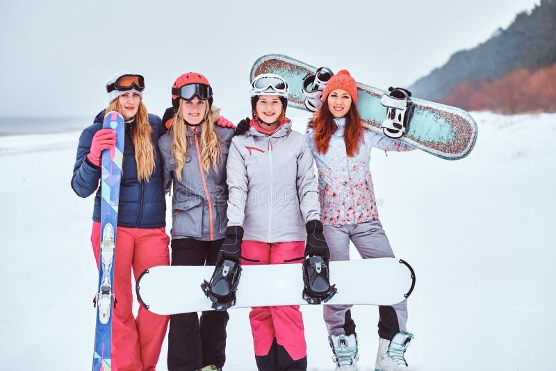 Rozochoceni kobieta przyjaciele w sport zimie odziewają z snowboards i nart pozować fotografia royalty free