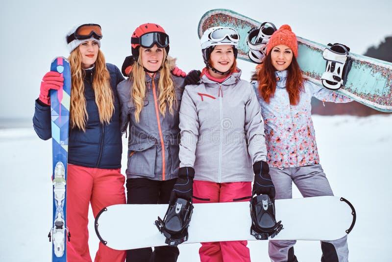 Rozochoceni kobieta przyjaciele w sport zimie odziewają z snowboards i nart pozować zdjęcie royalty free