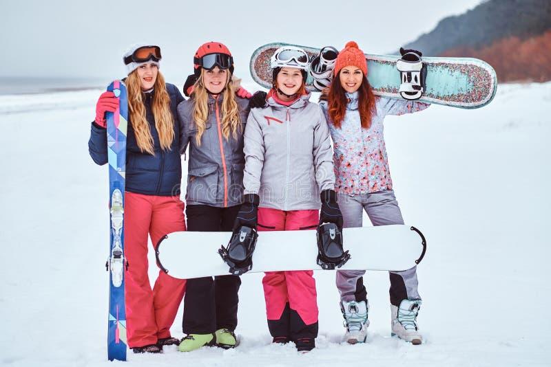 Rozochoceni kobieta przyjaciele w sport zimie odziewają z snowboards i nart pozować obrazy stock
