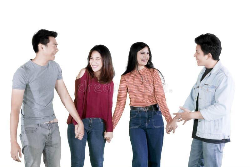Rozochoceni młodzi ludzie trzyma ręki na studiu obraz royalty free