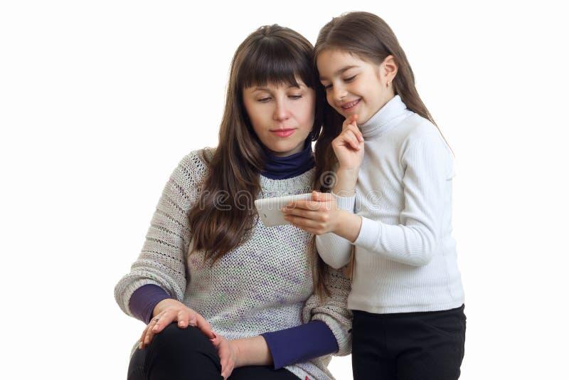 Rozochoceni małych dziewczynek przedstawienia ona macierzysty telefon komórkowy fotografia stock