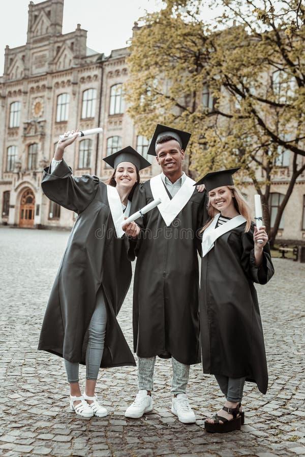 Rozochoceni międzynarodowi ucznie patrzeje prosto przy kamerą zdjęcie royalty free