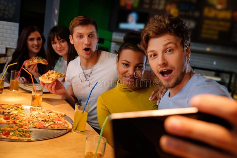 Rozochoceni multiracial przyjaciele bierze selfie w pizzeria zdjęcia stock